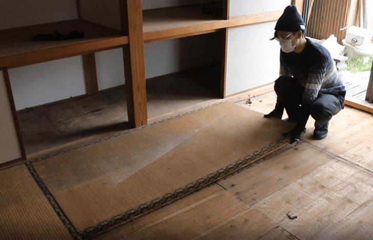 和室の畳を持ち上げようとする