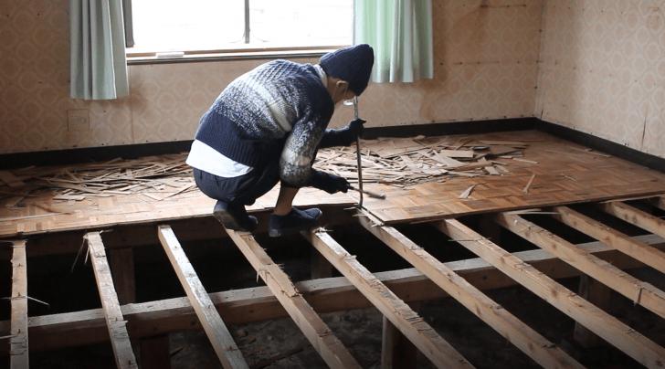 洋室の床を支える根太と下地合板の間にバールを差し込む