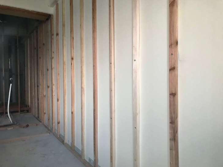 コンクリートの壁にハンマドリルで穴をあけて木材を取り付けた風景