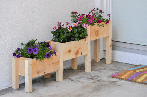 Pink and purple flowers in a tiered wooden planter box