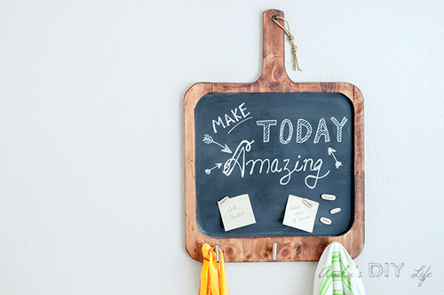 Hanging Wooden Chalkboard with magnetic notes on it and towels hanging on the hooks