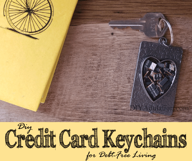 Heart Credit Card Keychain on Table Next to a Yellow Notebook with Text Overlay: DIY Credit Card Keychain for Debt-Free Living