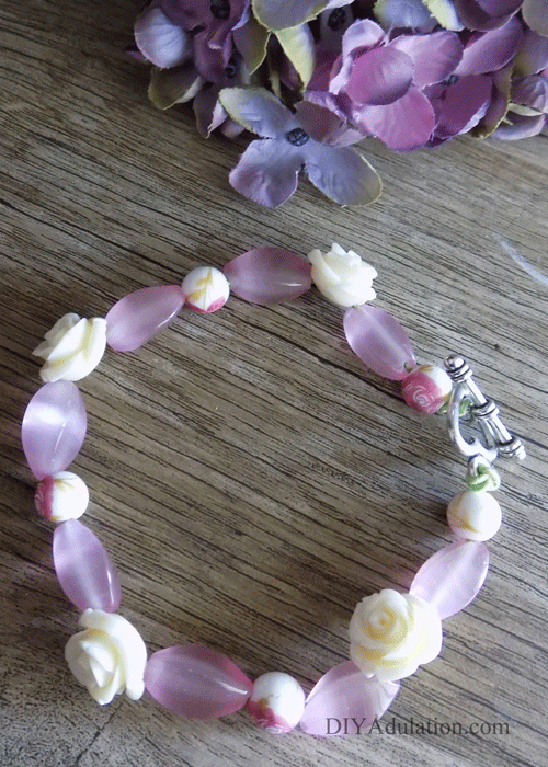 Pink floral beaded bracelet on wooden table