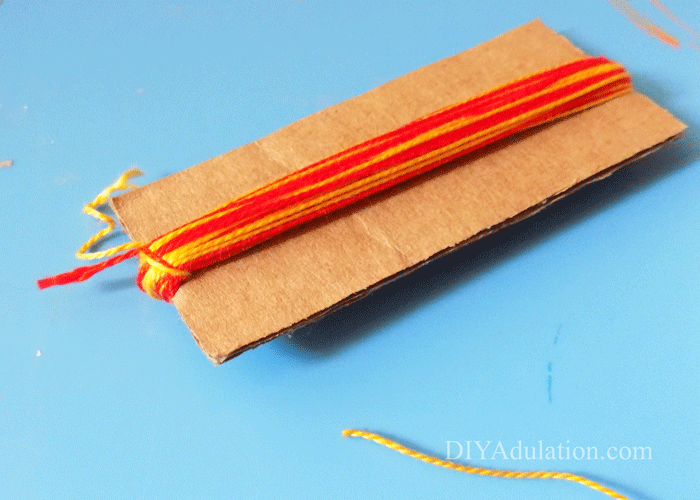 Red and yellow DMC floss wrapped around cardboard