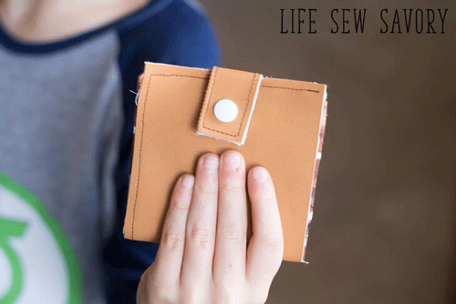 Child's hand holding a tan wallet