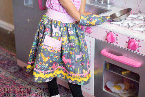 Little girl by a play kitchen wearing an apron and oven mitt