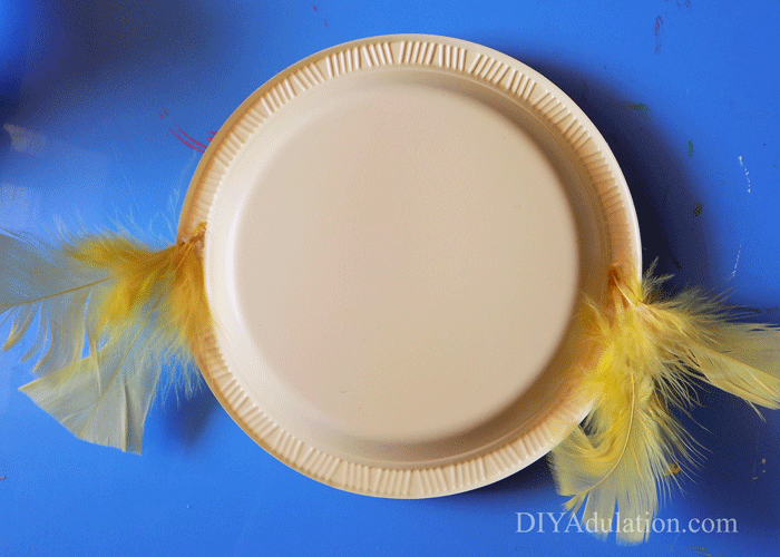 Yellow plastic plate with feathers on the sides