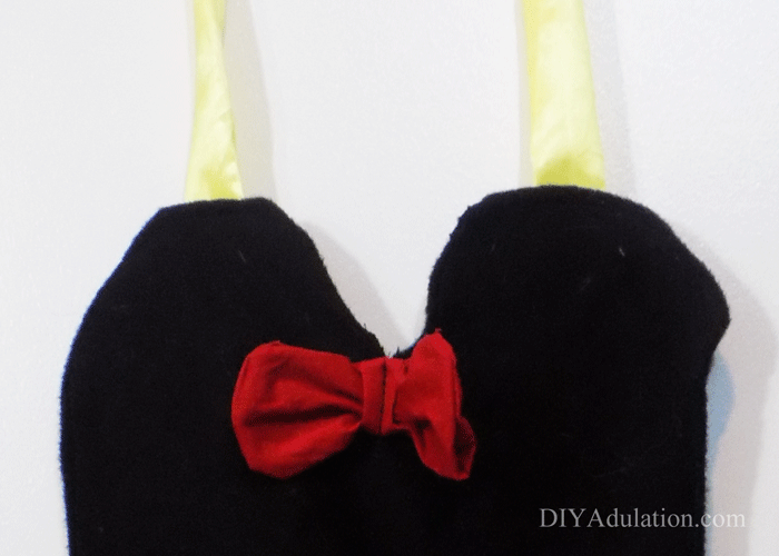 Close up of black apron top with red bow