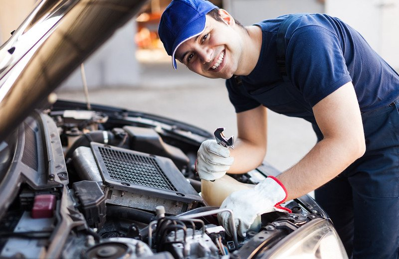 Auto mechanic holds a wrench standing by a car.