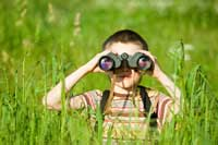 Boy looking through binoculars to review Big Future college search website