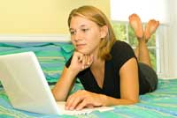 girl on bed with computer in community colleges with dorms