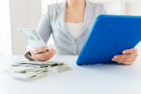 Woman with money looking at computer for college merit aid