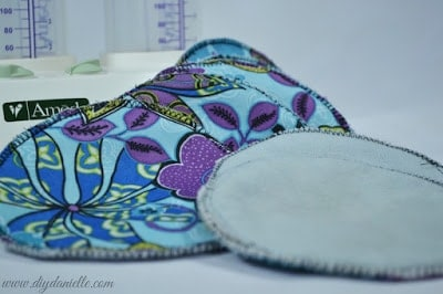 How to sew your own nursing pads without a serger. This is an easy sewing machine project to make a reusable product that will save you money. Pictured: Blue floral DIY nursing pads with breast pump in the background.