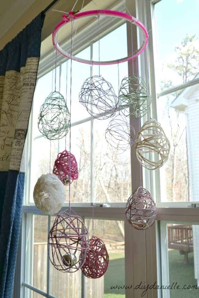 Our Easter Egg Wind Chime DIY, hanging from a curtain rod.