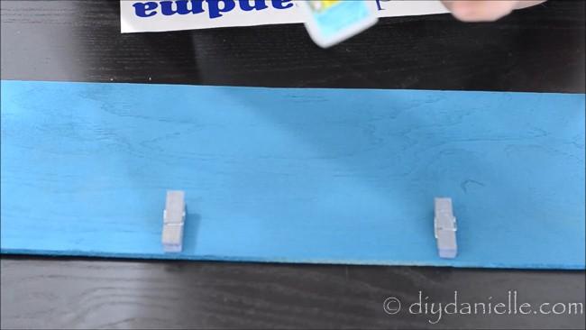 Glue clips onto children's art display.