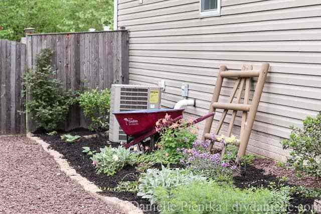 Garden path with red stone, upcycled wheelbarrow, and columbine.