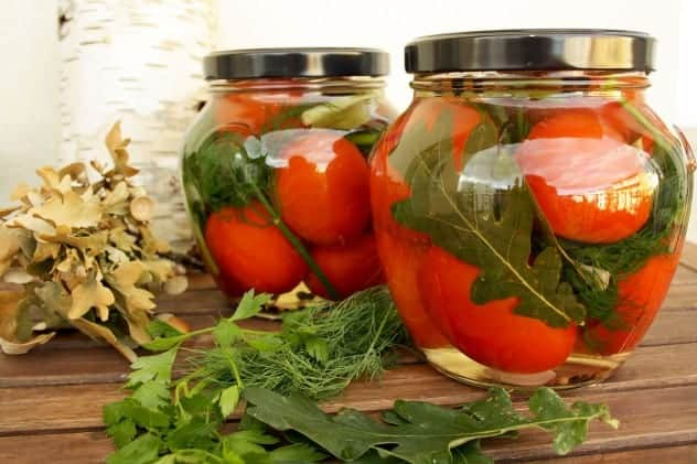 Pretty pickled tomatoes in jars.