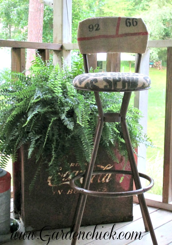 A rusty bar stool is transformed with burlap fabric - by Garden Chick