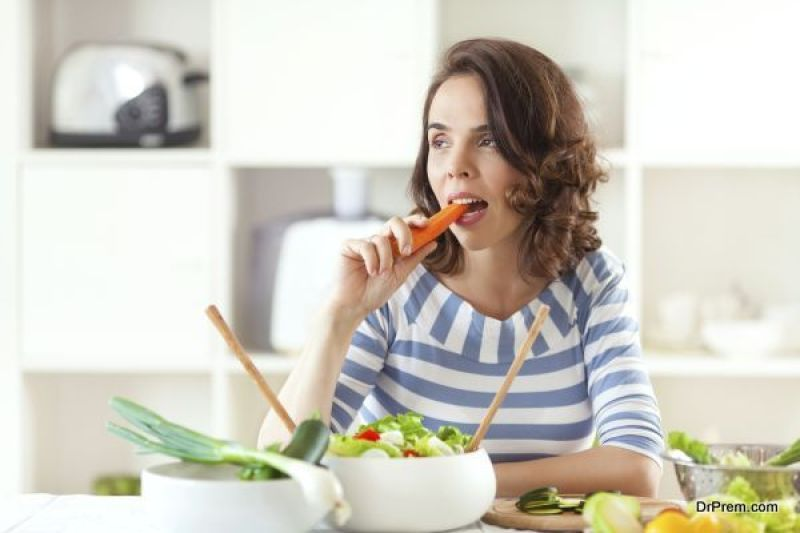 Woman is eating carrot