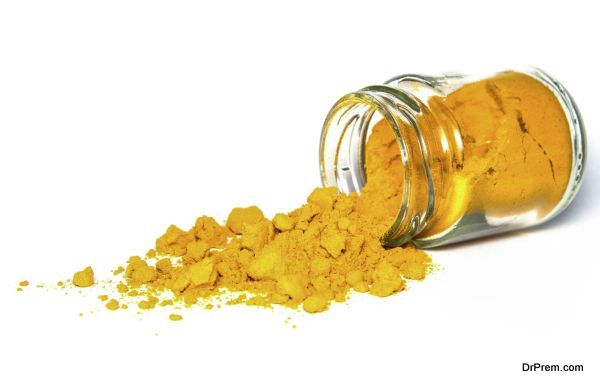 Spilled dose of turmeric spice powder isolated on white background