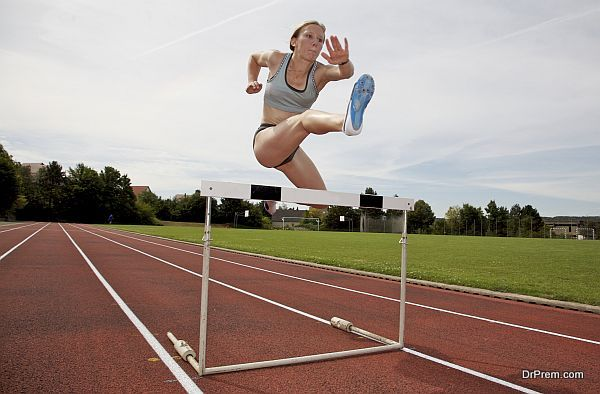 A young athlete jumping over a hurdle