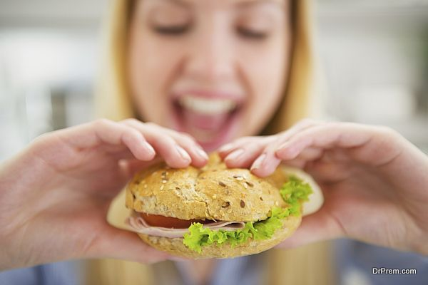 Closeup on happy young woman eating burger