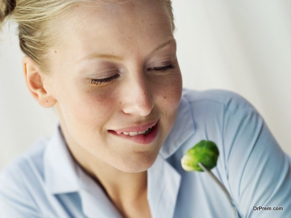 Young woman looking at a Brussels sprout on a fork