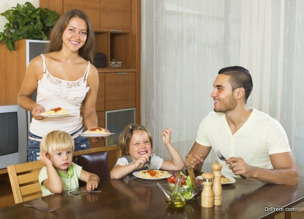 Happy ordinary family of four eating spaghetti at home interior