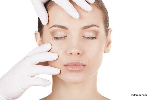 Preparation before facial surgery. Beautiful young woman keeping eyes closed while doctor in medical gloves examining her face isolated on white