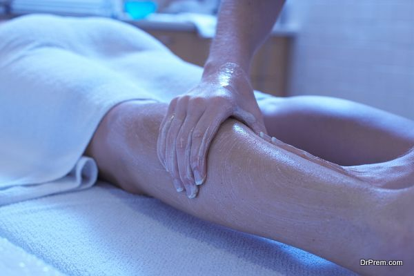 Woman receiving leg massage with lotion at spa