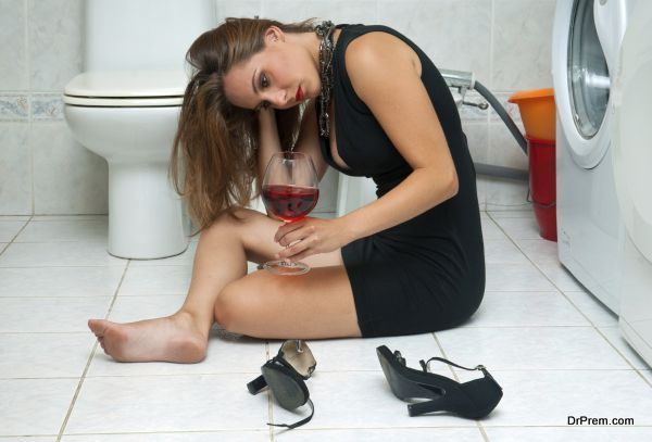 attractive drunk woman in her bathroom with glass of red wine
