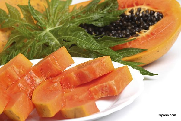 Ripe papaya, slices with seeds and green leaf