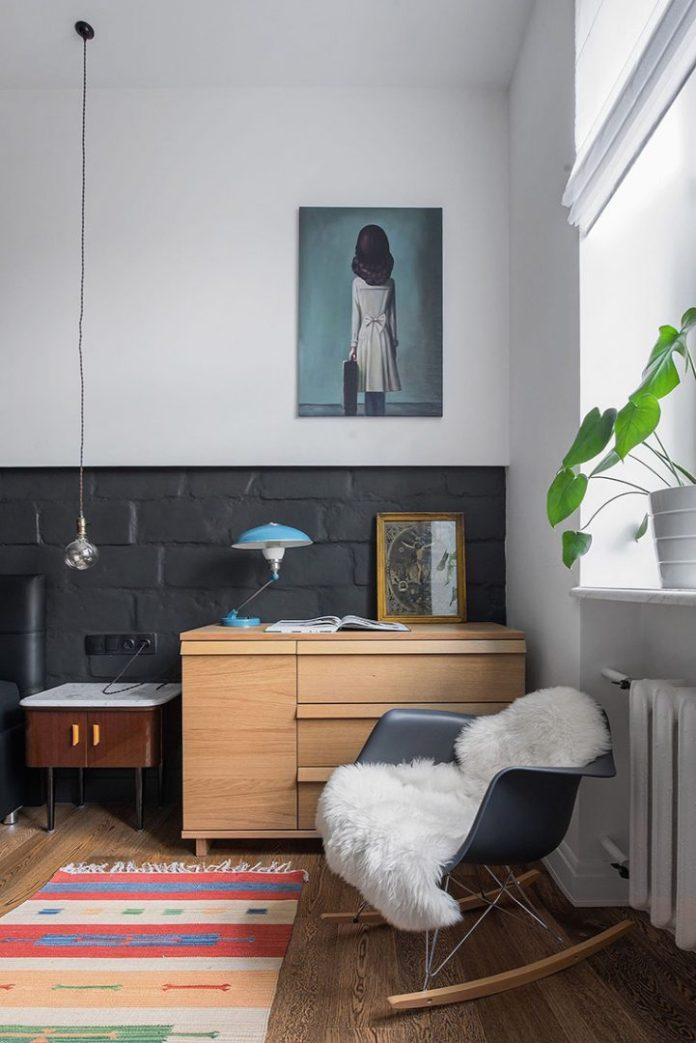 Apartamento urbano/industrial. Quarto com comoda de madeira, cadeira de balanço eames e metade da pareda na cor preta