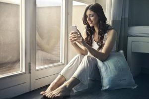 woman sitting beside window at home holding phone