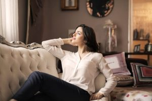 woman in white dress shirt and black pants lounging at home