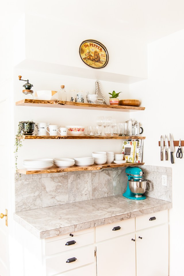 Kitchen makeover featuring white cabinets, and floating shelves made from live-edge wood. #kitchen #openshelves #DIY #openshelving