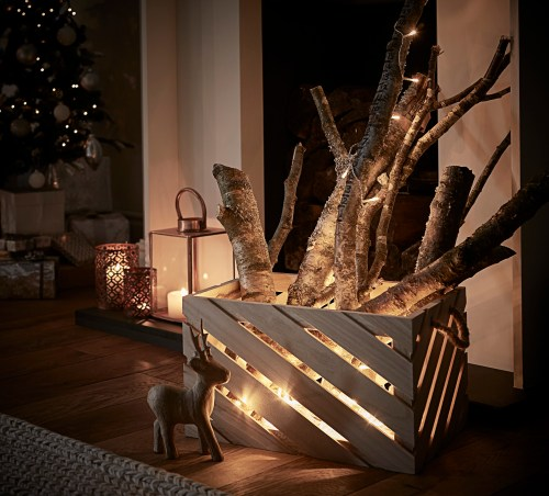 Simple DIY holiday decor ideas using white lights: crate + logs + lights