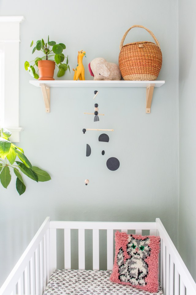 DIY mobile in a blue, pink, and terracotta gender-neutral nursery