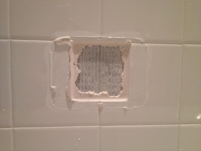 broken tile soap dish in a shower