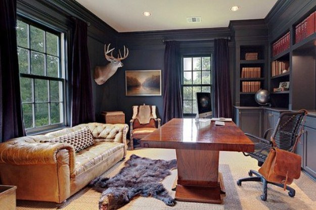 Men's office lounge with dark walls, leather, and bear rug | 10 Man Cave Ideas For Real Men