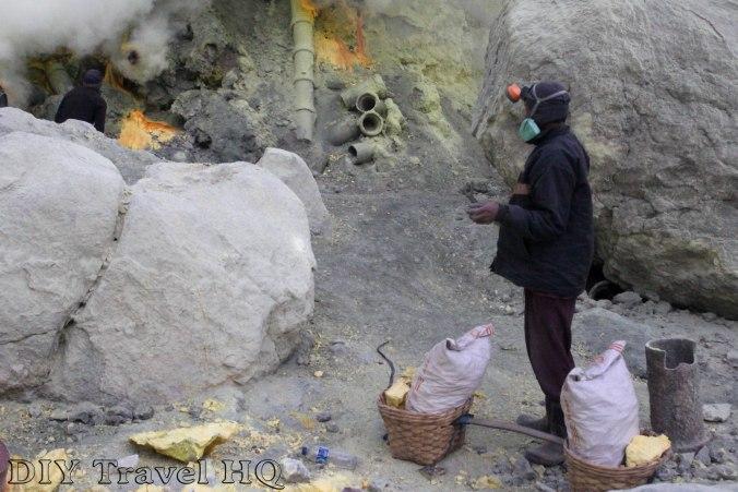 Miner breaking sulphur from the crater of Mt Ijen