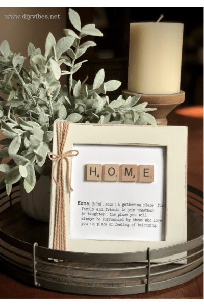 scrabble tile framed art on a tray with a plant and a candle.