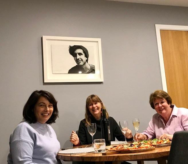 Three women sitting around a table, watched over by a black and white portrait of a young man