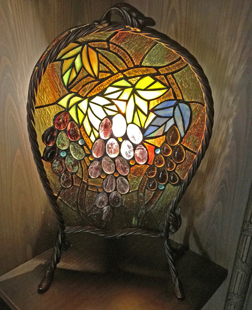 Stained glass light fixture featuring artwork grapes at Disneyland Club 33
