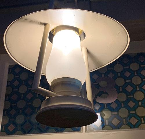 Lantern shaped light fixture hanging in Crockett and Russel Hat Co in Disneyland Frontierland