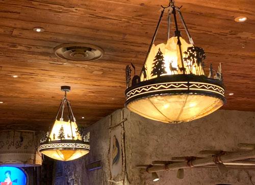 Old West ceiling light fixture depicting wildlife and trees in Pioneer Mercantile in Disneyland Frontierland