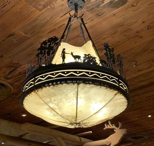 Vintage ceiling light fixture depicting wildlife and trees in Pioneer Mercantile in Disneyland Frontierland