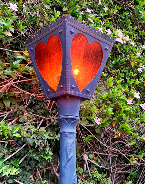 Heart shaped light fixture on lamppost near Alice in Wonderland attraction in Disneyland