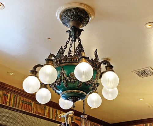 Green and gold ornate light fixture chandelier at Chester Drawer's on Main Street USA in Disneyland