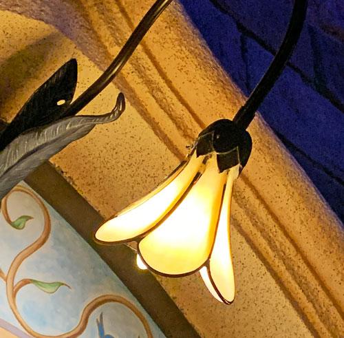 Flower shaped yellow light fixture on outside of Sleeping Beauty Castle in Fantasyland Disneyland